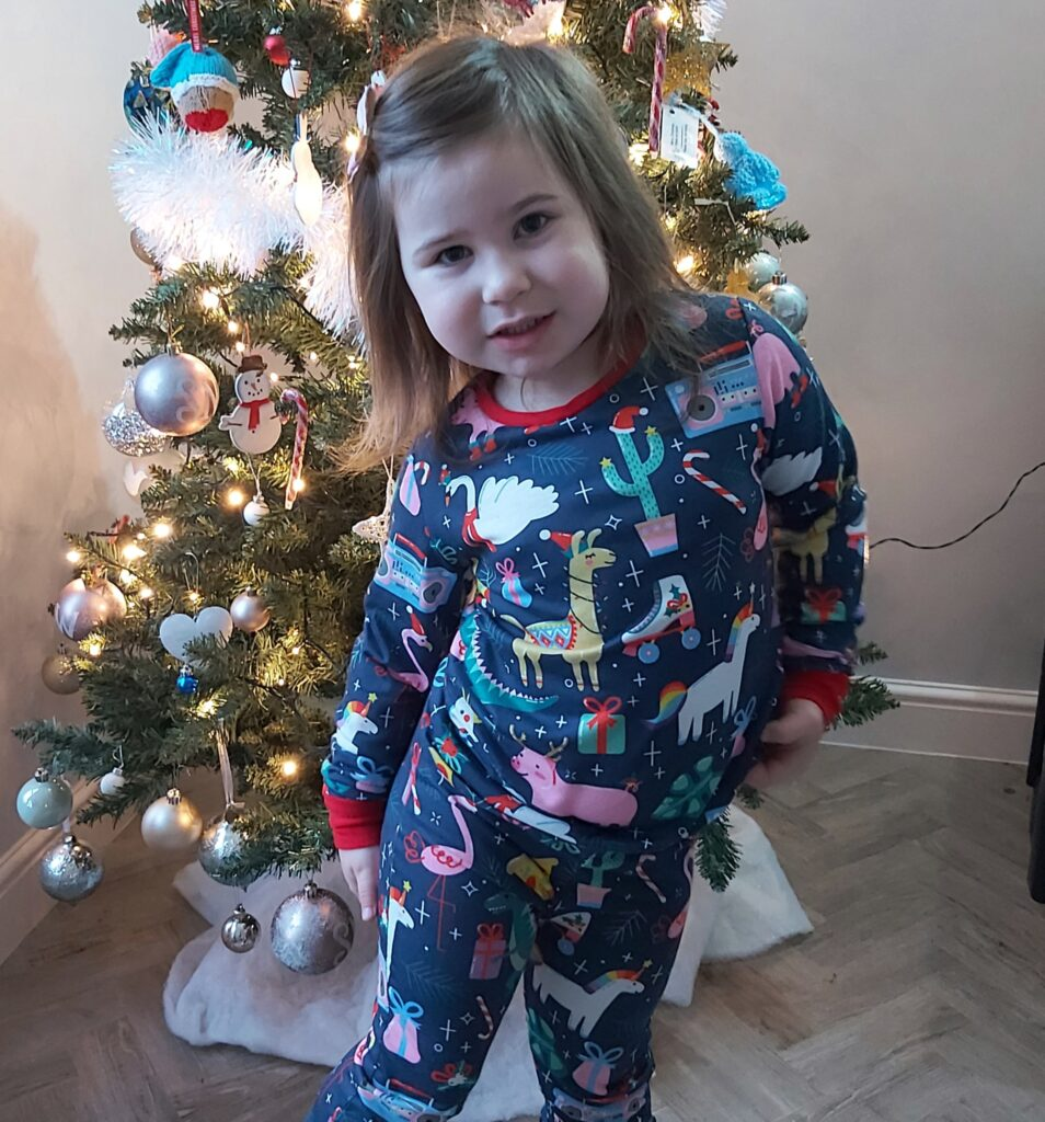 Ava stands in front of a christmas tree, wearing fun christmas patterned pyjamas. There are festive llamas, pigs, with antlers, and other christmassy pictures on them.